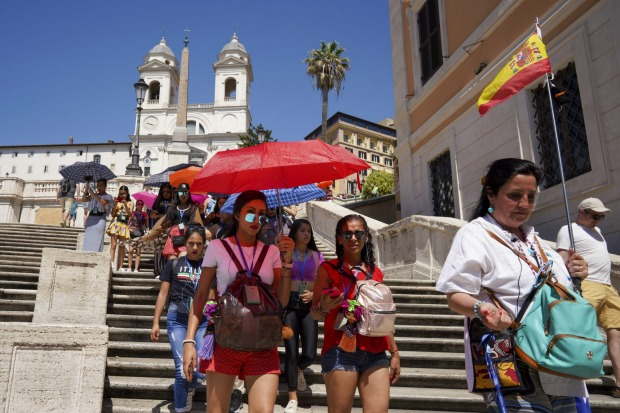 Tourists shelter from the sun as they walk down the Spanish Steps in Rome.