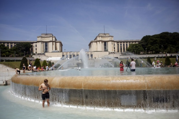 People cool off in the fountain of the Trocadero, in Paris.