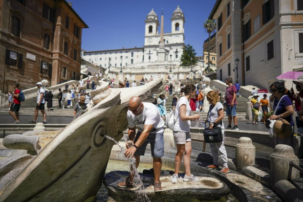 Tourists cool-off in Bernini's 17th-century Barcaccia fountain, at the foot of the Spanish Steps, in Rome.