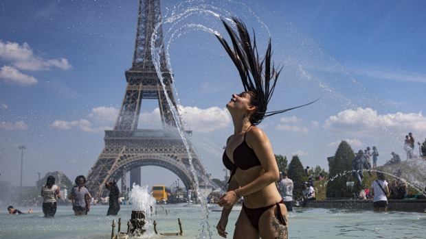 A girl cools down in the fountains of Trocadero, across from the Eiffel Tower, during a heatwave in Paris last year.