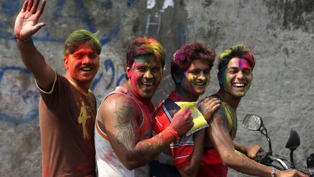 Young men with their faces smeared with coloured powder as they ride a motorbike during Holi festivities in Mumbai.