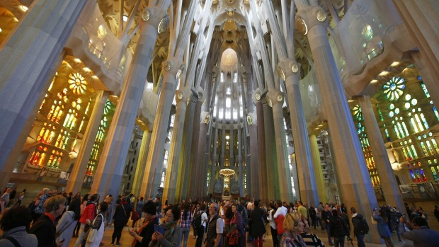 FILE - In this Wednesday, Oct. 21 2015 file photo, tourists visit the Sagrada Familia church in Barcelona. Spain. Venice is planning to divert massive cruise liners while Barcelona has cracked down on apartment rentals and initiated a holistic approach to managing its status as a tourism city. Both are at the forefront of efforts to get a grip on