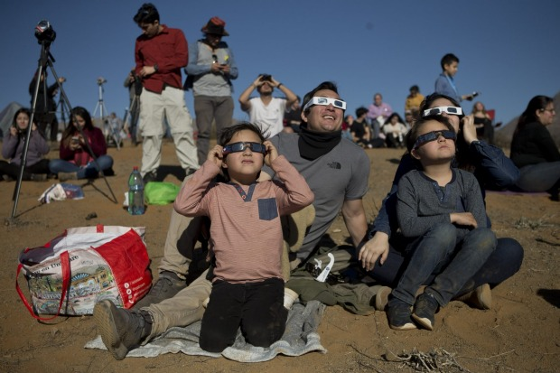 People watch a total solar eclipse in La Higuera, Chile. Tourists from around the world gathered to witness the cosmic ...
