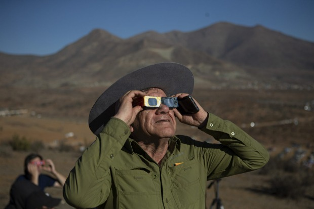 A man looks up at a total solar eclipse in La Higuera, Chile. Tourists from around the world gathered to witness the ...