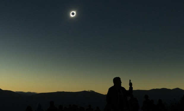 A man stands under a total solar eclipse in La Higuera, Chile. Tourists from around the world gathered to witness the ...