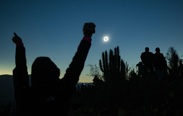 People view a total solar eclipse from La Higuera, Chile. Tourists from around the world gathered to witness the cosmic ...