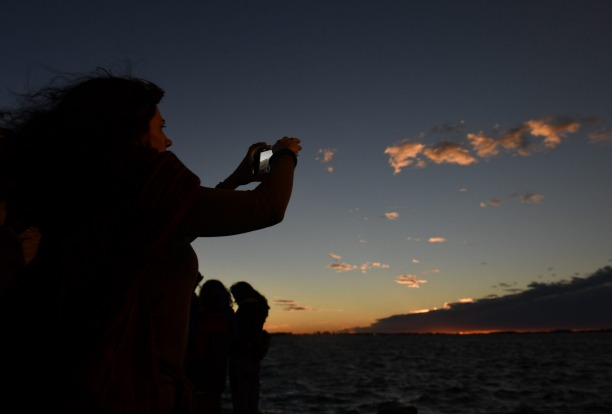 A woman takes pictures of a total solar eclipse in Chascomus, Argentina. Tourists from around the world gathered to ...