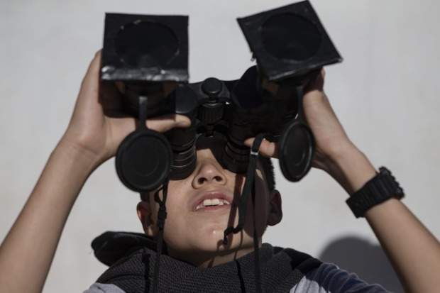 A youth tests special binoculars to view the total solar eclipse. Tourists from around the world gathered to witness the ...