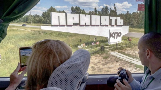 A tour bus, operated by Chornobyl-Tour, drives past a Soviet-era sign marking the entrance to the abandoned city of Pripyat.