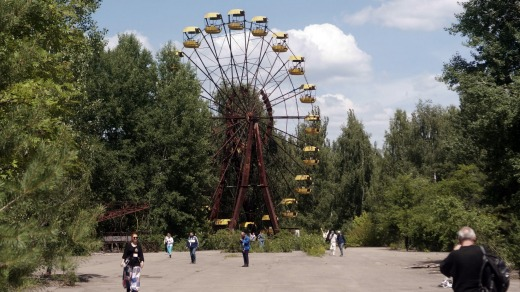 Tourists explore the abandoned amusement park and ferris wheel in Pripyat.
