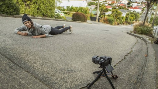 Marine Chabrol, a tourist from France, lies in the middle of Baldwin St, Dunedin.