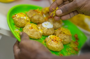 A Mumbai street-food hawker garnishes pani puri - fried pastry shells stuffed with chutney, potato, herbs and spices.