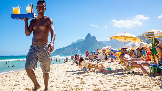 A beach vendor selling caipirinhas calls out to  customers on Ipanema Beach with Two Brothers mountain backdrop.