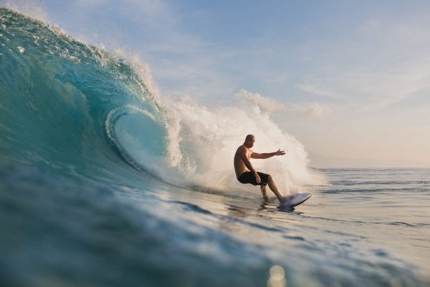 HANG 10 Catch a wave just as red skies sink into sparkling waters in the shadow of the mesmerising Mount Agung volcano, ...