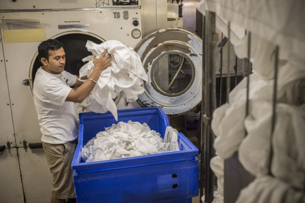 On Deck 1, three crew are in working in the laundry on board P&O Pacific Explorer.