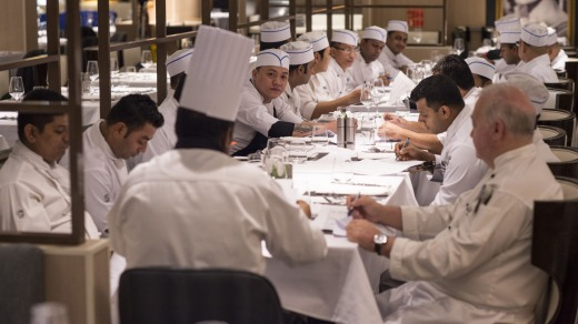 Chefs are meeting for the day's menu briefing.