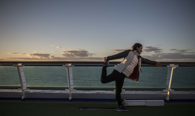 A passenger stretches at sunrise on the deck of the PP&O Pacific Explorer.