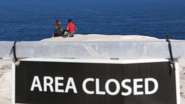 Tourists ignoring the signs and fences around Wedding Cake Rock, NSW.