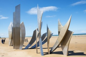 Visitors to Omaha Beach walk around the sculpture entitled The Braves, created for the 60th anniversary of D-Day in 2004.