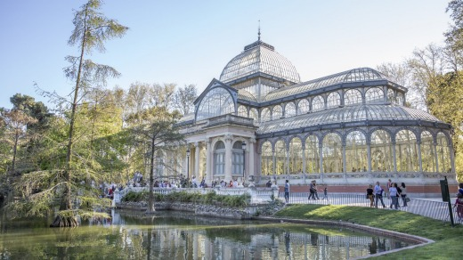Tourists and locals gather outside the Crystal Palace in the Retiro Park in Madrid.