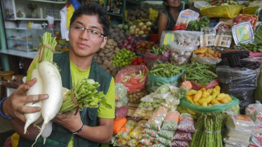 A vegetable vendor at Lima's Surquillo market, start of the culinary adventure.
