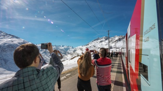Passengers take photos from the Glacier Express, Switzerland.