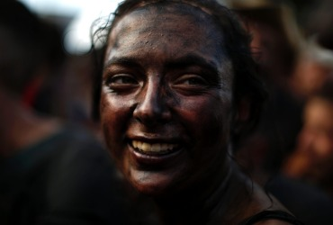 A woman painted with black grease smiles as she takes part at the traditional festivities of the Cascamorras festival in ...