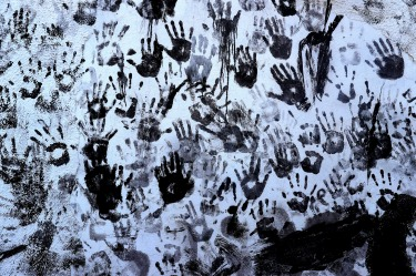 Hand prints are made by people painted with black grease on a wall during the traditional festivities of the Cascamorras ...
