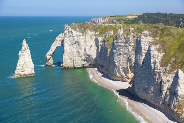 Etretat: Blanketed in bright green grass, Etretat's white cliffs have been eroded to create archways and needles ...