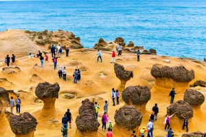 Many tourists walk around the stone shapes at Yehliu Geopark.