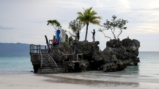 People pose for pictures on the Boracay Grotto also known as 'Willy's Rock'.