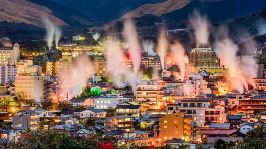 Hot spring bath houses with rising steam in Beppu, Japan.