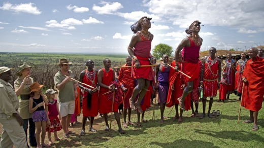 A family watches a group of Maasai warriors in Kenya.