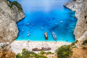 Tourists and tourist boats  in the famous Navagio Bay on Greece's Zakynthos island.