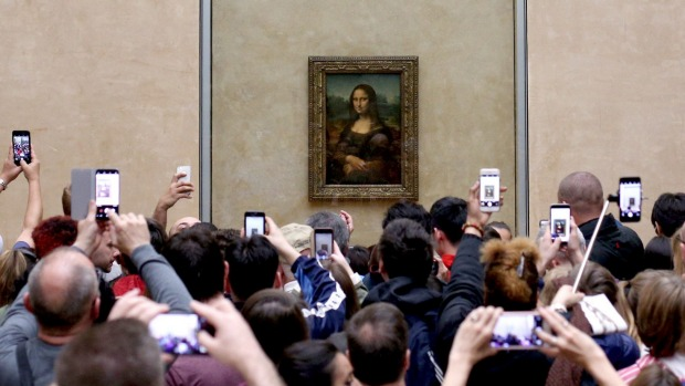 Most visitors tend to take photos of the famous painting, rather than just look at it.