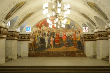 Kiyevskaya station. It features low, square pylons faced with white marble and large mosaics.