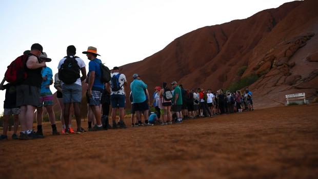 Tourists are seen lining up to climb Uluru.