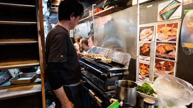 A chef grills meat skewers at an izakaya in Tokyo's Shibuya district.