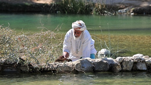 A man in a waterpool in Wadi Bani Khalid, Oman.