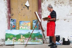 Artists paint what they see on a street in Paraty.