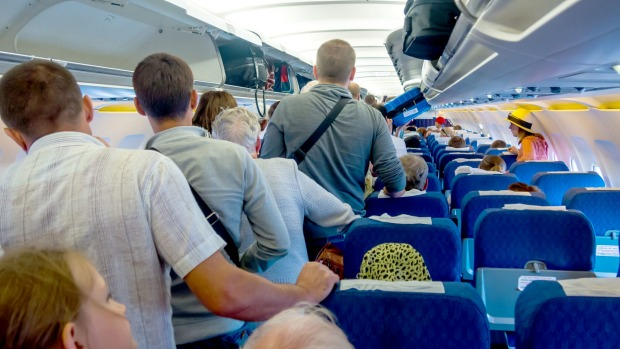 Despite being asked to remain in their seats while the rows in front disembark, passengers are still getting up as soon ...