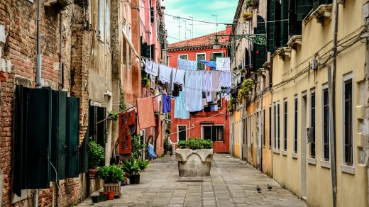 Clothes hanging across buildings on a narrow alley in Venice.