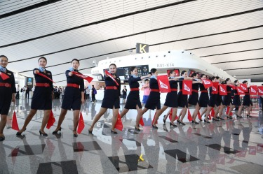 Staff members of China United Airlines perform at Beijing Daxing International Airport during its first day of operation ...