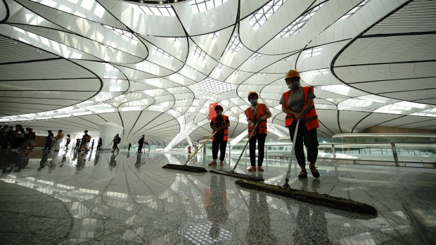 Cleaners work at the Beijing Daxing International Airport during a construction completion ceremony in June.