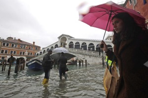 People walk near the Rialto bridge on the occasion of a high tide.