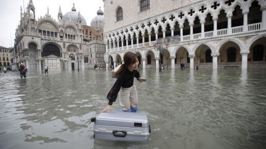 A tourist pushes her floating luggage in a flooded St. Mark's Square.
