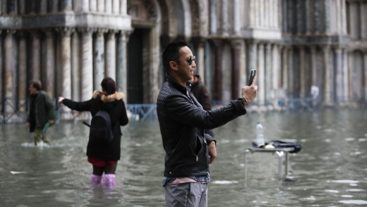 Tourists take pictures in a flooded St. Mark's Square.