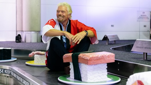 Sir Richard Branson rides the 'giant sushi train' Brisbane Airport during a media event announcing Brisbane to Haneda ...
