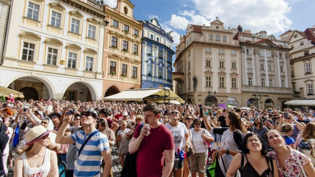 Thousands of tourists visit Prague's old town during peak season.