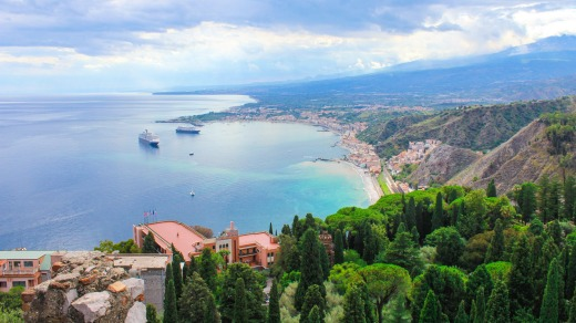 From the old ruis of Taormina, tourists can see the bay of Sicily.